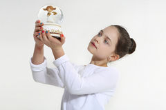 Little girl holding. Glass figurine Royalty Free Stock Images
