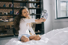 Little girl holding alarm clock while sitting on bed stock images