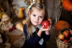 Little girl holding an apple in an autumn interior stock images