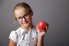 Little girl is holding an apple stock images