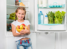 Little girl holding apples from fridge Stock Photography
