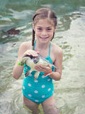 Little Girl holding a baby sea turtle Stock Photos