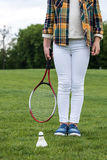 Little girl holding badminton racquet and standing on green grass with shuttlecock Stock Image