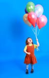 Little girl holding balloons Stock Image