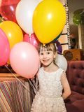 Little girl holding balloons. The child smiles cheerfully on a holiday. royalty free stock photos