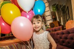 Little girl holding balloons. The child smiles cheerfully on a holiday. royalty free stock photo