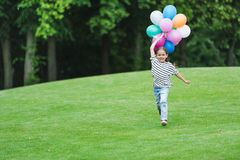 Little girl holding balloons and running in park. Cheerful little girl holding balloons and running in park Royalty Free Stock Photos