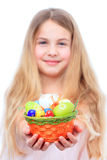 Little girl holding a basket with easter eggs. Little girl giving a basket filled with easter eggs focus on the basket Stock Image