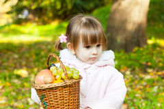 Little girl holding a basket full of fruit Stock Image