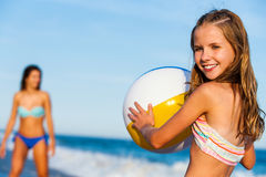 Little girl holding beach ball with mother in background. Stock Image