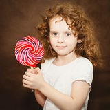 Little girl holding big colorful lollipop Stock Photo