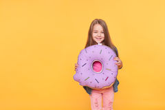 Little girl holding a big donut over yellow background. Little girl holding big donut over yellow background. Cute preschool kid smiling with giant null numeral royalty free stock photos