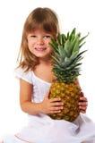 Little girl holding big pineapple Stock Image
