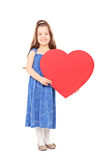 Little girl holding a big red heart Royalty Free Stock Image