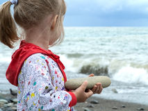 Little girl holding a big rock Stock Image
