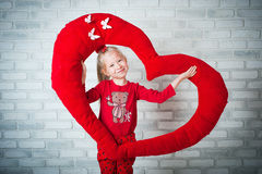 Little girl holding big toy heart Stock Photo