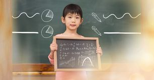 Little girl holding blackboard with math equations and diagrams. Digital composite of Little girl holding blackboard with math equations and diagrams royalty free stock photos