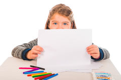 Little Girl Holding a Blank Piece of Paper. A little girl showing a piece of paper. Colored crayons and paint on the table Royalty Free Stock Photography
