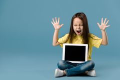 Little girl holding a blank tablet computer. Cute little child girl holding blank tablet computer and screaming on blue background royalty free stock photos