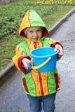 Little girl holding blue bucket and shovel. Under rain Royalty Free Stock Photography