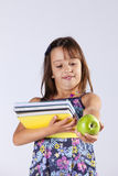 Little girl holding books and a apple Stock Photos