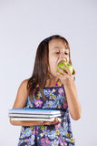 Little girl holding books and a apple Stock Photo