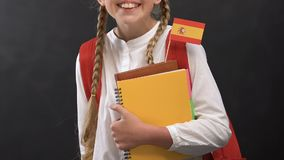 Little girl holding books with Spanish flag and smiling at camera, language. Stock footage stock video