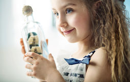 Little girl holding a bottle with a ship Stock Images