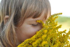 A little girl holding a bouquet of field summer flowers and smelling it with her eyes closed Royalty Free Stock Image