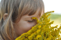 A little girl holding a bouquet of field summer flowers and smelling it with her eyes closed Stock Image