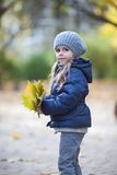 Little girl holding the bouquet from leaves Stock Photography
