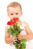 Little girl holding a bouquet of red roses. Little girl holding a bouquet of flowers for mom Royalty Free Stock Photography