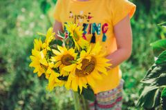 Little girl holding a bouquet of sunflowers stock images