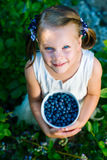 Little girl holding a bowl of blueberries - shallow depth of f Stock Photo