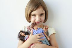 Little girl holding boy and girl dolls Royalty Free Stock Photo