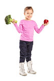 Little girl holding a broccoli and an apple Stock Photo
