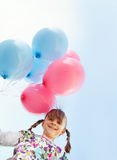Little girl holding a bunch of balloons stock image