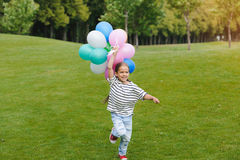 Little girl holding bunch of colorful balloons and running in park. Cute little girl holding bunch of colorful balloons and running in park Stock Image
