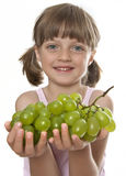 Little girl holding a bunch of grapes Stock Images