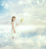 Little girl holding a butterfly. On the clouds royalty free stock photo