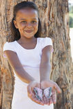 Little girl holding a butterfly in the park smiling at camera Royalty Free Stock Photos