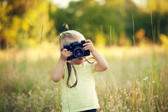Little girl holding a camera. On nature royalty free stock image
