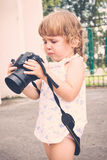 Little girl holding a camera and taking pictures. Stock Photo