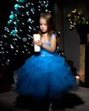 A little girl is holding a candle. A little girl in a dark room, on Christmas night, with a burning candle in her hands. Concept of a holiday, Christmas, family Stock Photos