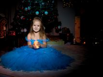 A little girl is holding a candle. A little girl in a dark room, on Christmas night, with a burning candle in her hands. Concept of a holiday, Christmas, family Stock Image