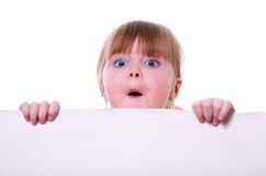 Little girl holding a cardboard looking surprised. Isolated little girl holding a cardboard looking surprised Stock Photography