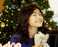 Little girl holding cash at Christmas Royalty Free Stock Photos