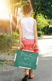 Little girl holding chalkboard with words back to school. Outdoor photo Royalty Free Stock Photo