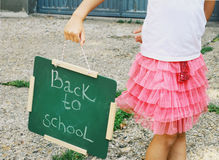 Little girl holding Chalkboard with words Back to School. Outdoor photo Stock Photos