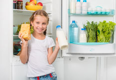 Little girl holding cheese and milk Royalty Free Stock Images